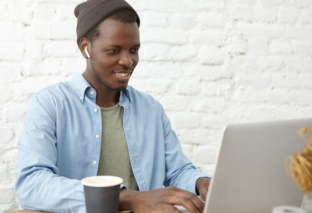 Positive stylish young Afro American copywriter in hat wearing wireless earbuds chatting with his boss via video conference call on generic laptop computer, looking at screen and smiling cheerfully